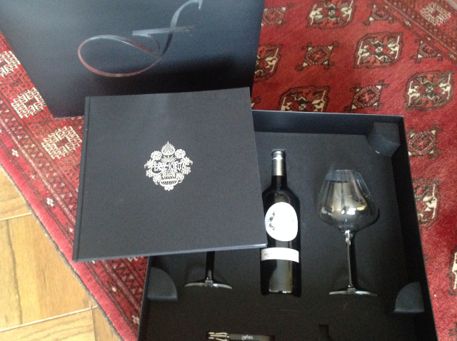 A wine bottle, a book & two glasses are inside
